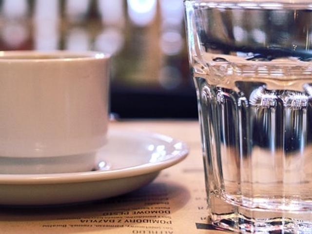 Eine Kaffeetasse und ein Glas Wasser auf einem Tisch