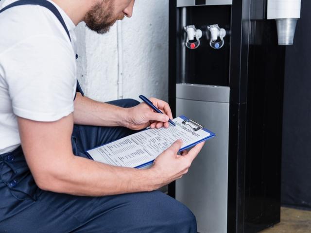 Ein Handwerker mit einer Checkliste vor einem Wasserspender
